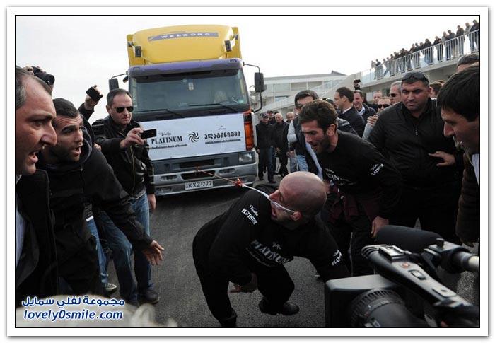 رجل يجر شاحنة بأذنه