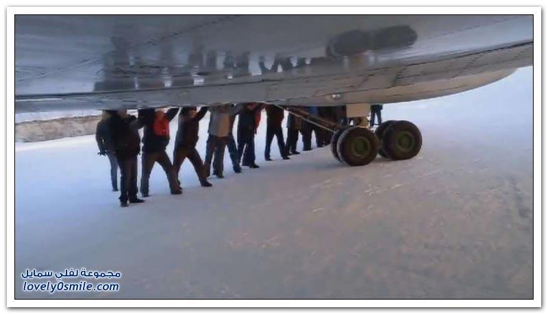 ركاب طائرة ينزلون من الطائرة ويدفعونها بأيديهم بسبب تجمدها